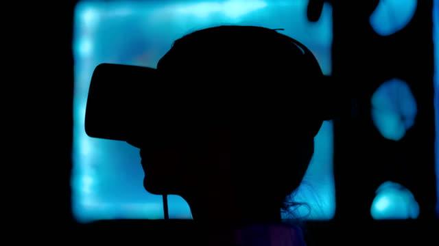 giovane donna che usa cuffie per la realtà virtuale alla mostra interattiva dark - computer indossabile video stock e b–roll