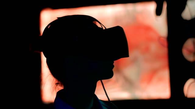vídeos y material grabado en eventos de stock de mujer joven usando auriculares de realidad virtual en la exposición interactiva oscura - exhibir