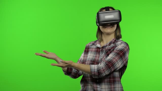 Young woman using VR headset helmet to play game, showing side advertising area. Chroma key