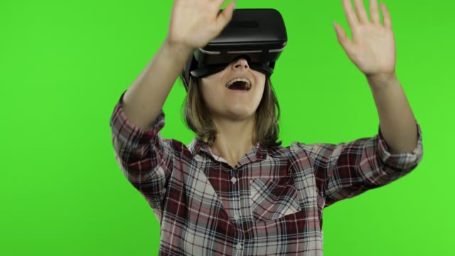 Young woman using VR headset helmet to play game. Watching virtual reality 3d 360 video. Chroma key