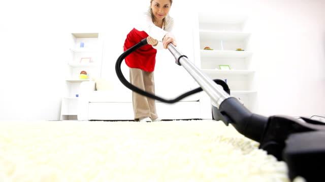 giovane donna con aspirapolvere il suo soggiorno. - moquette video stock e b–roll