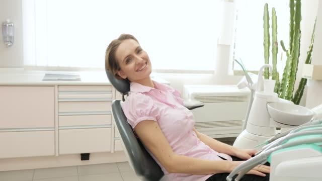 vídeos y material grabado en eventos de stock de mujer joven visita al dentista - ortodoncista