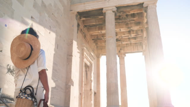 Young Woman visiting Parthenon, Acropolis of Athens, Greece. Large hat, fashion white dress, sunglasses, vintage camera. Young Woman visiting Parthenon, Acropolis of Athens, Greece. Large hat, fashion white dress, sunglasses, vintage camera. greek architecture stock videos & royalty-free footage