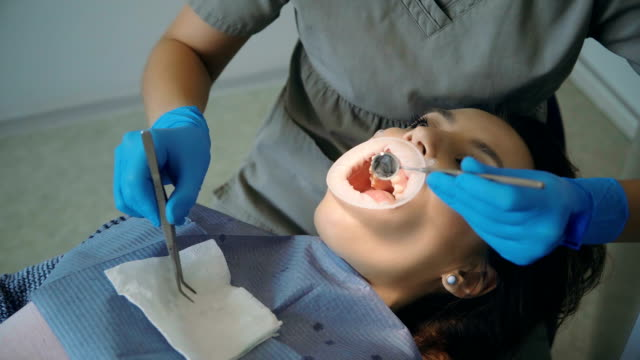 vídeos y material grabado en eventos de stock de mujer joven visitando el consultorio dental. mujer en sillón dental, el doctor pulido y la limpieza de los dientes - ortodoncista