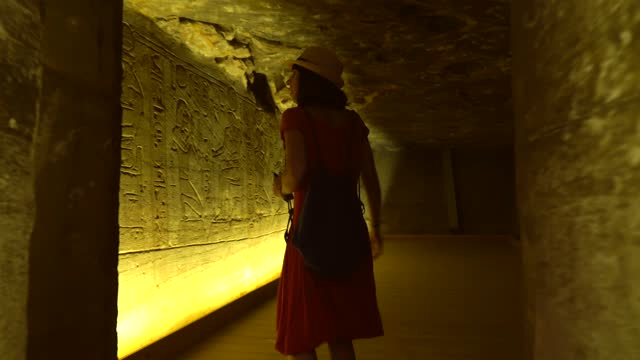 A young woman visiting the inner rooms inside the temple of Abu Simbel, in southern Egypt in Nubia next to Lake Nasser. Temple of Pharaoh Ramss II, 4k video