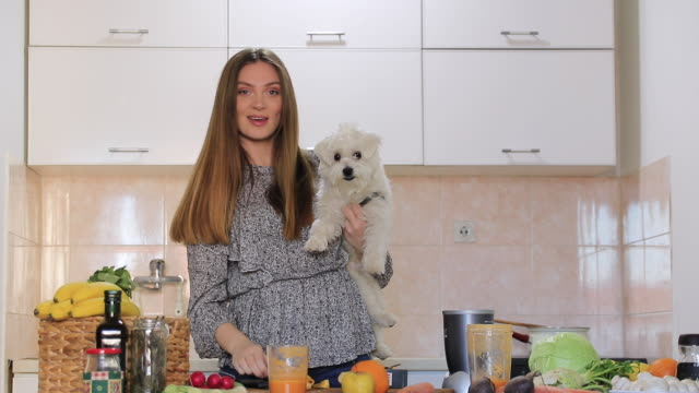 Young woman vlogging with her Maltese dog