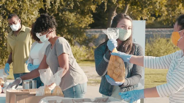 genç kadın gıda perve sırasında aile ile gönüllü - giving tuesday stok videoları ve detay görüntü çekimi