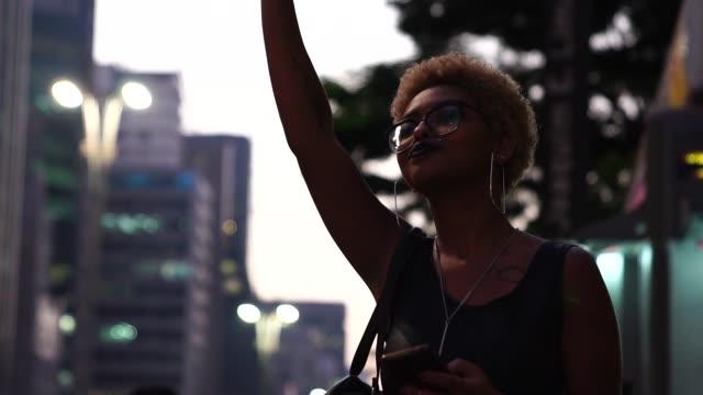 Junge Frau wartet auf das öffentliche Verkehrsmittel/Taxi – Video