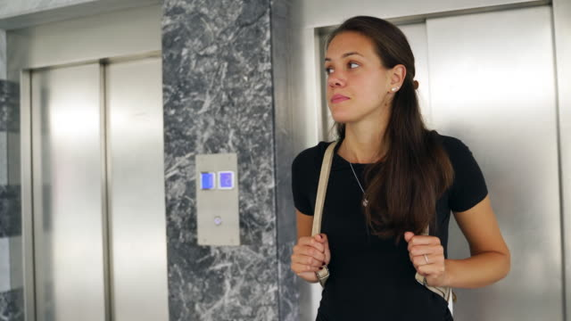 Young Woman Waiting in Front of Elevator and Looking Around video