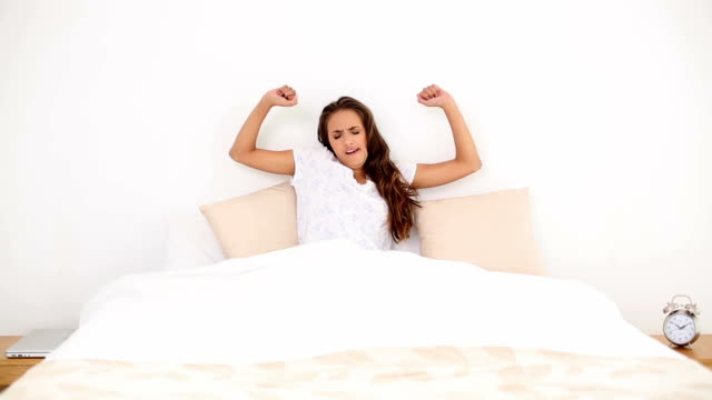 Young woman waking up and yawning in her bed video