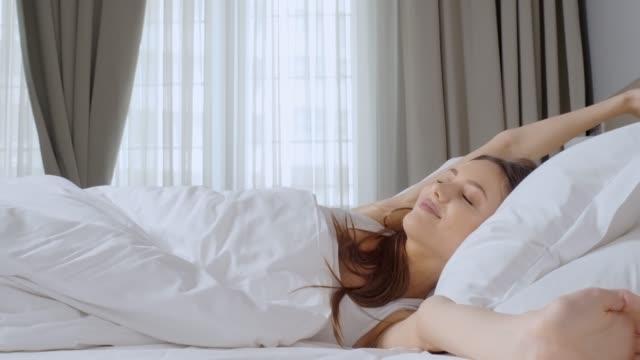 młoda kobieta budzi się. - drzemać filmów i materiałów b-roll