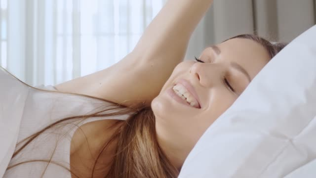 young woman waking up. - pillow stock videos & royalty-free footage