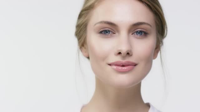 young woman walking against white background - trattamento per la pelle video stock e b–roll