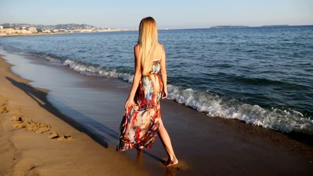 若い女性は海に沿って歩く ビデオ