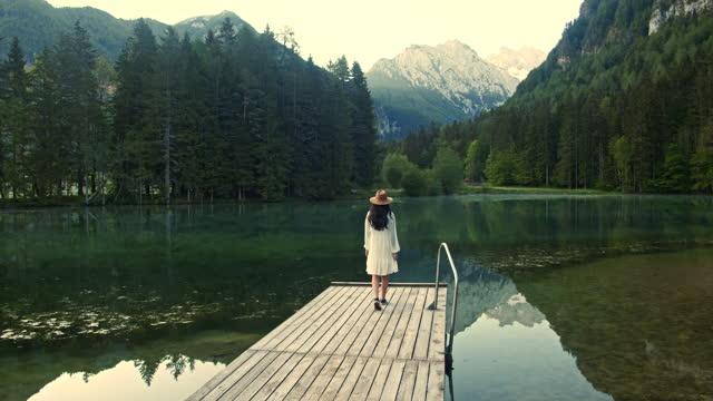 vídeos de stock, filmes e b-roll de câmera lenta jovem caminhando ao longo da doca de madeira no lago - eslovênia