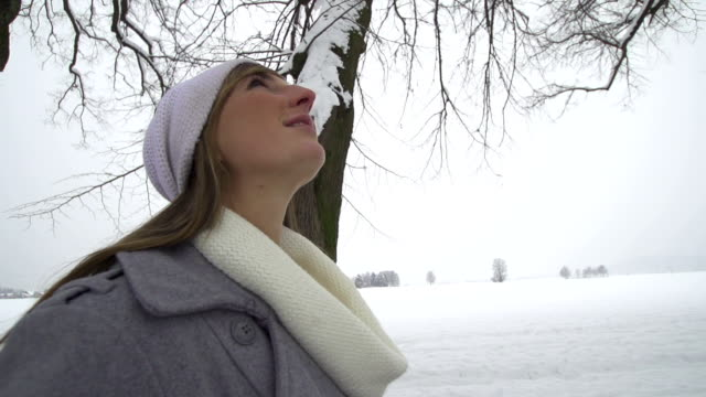 SLOW MOTION: Young woman walking along winter tree promenade video