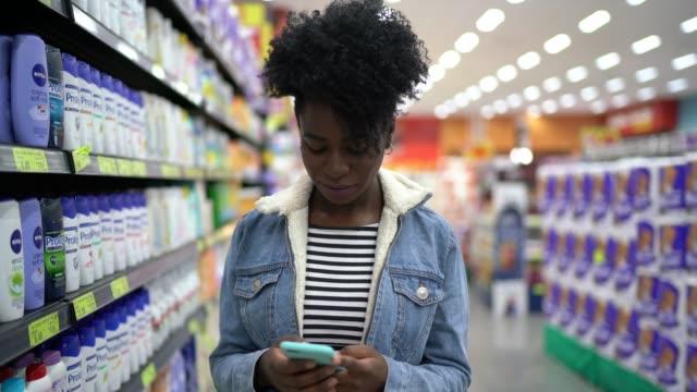 젊은 여자 산책 과 사용 휴대 전화 에 슈퍼마켓 - 쇼핑 스톡 비디오 및 b-롤 화면