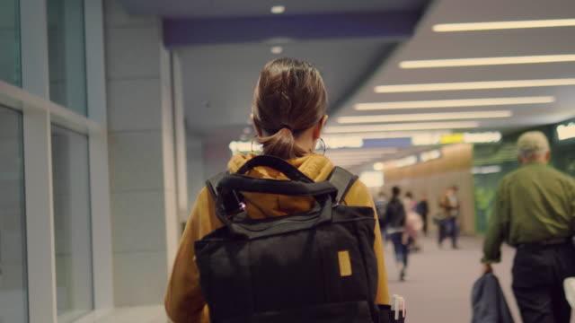 young woman walking at airport. - турист с рюкзаком стоковые видео и кадры b-roll