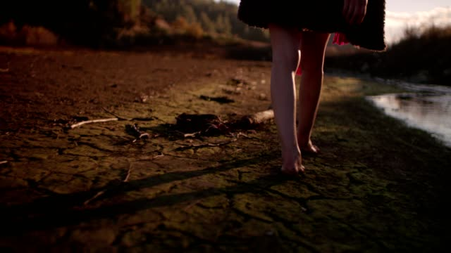 Young woman walking barefoot across cracked earth in mountains video