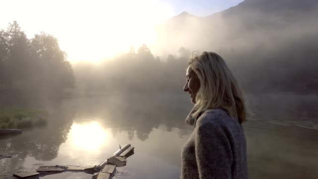 Young woman walking by the lake at sunrise, morning fog video