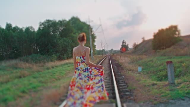 Young woman walking down railroad video