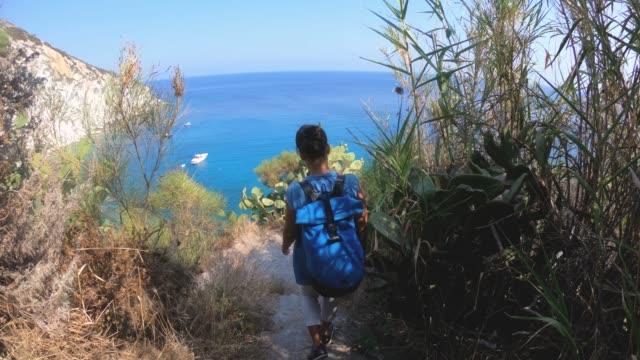 vídeos de stock e filmes b-roll de young woman walking down stone stair path to a bay on ponza island coast cliff. - mochila saco