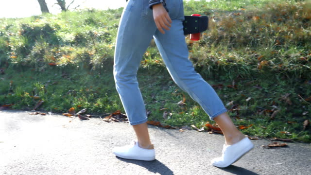 Young woman walking in a park carrying skateboard