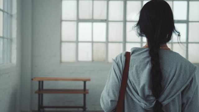 young woman walking in ballet studio - od tyłu filmów i materiałów b-roll