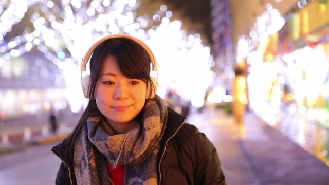 Young woman walking in city for shopping at Christmas night