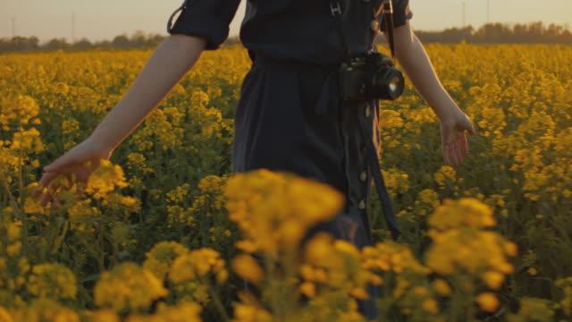 SLO MO MS TS Young woman walking in field of rape