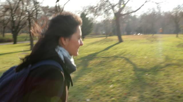 vídeos de stock e filmes b-roll de young woman walking in park with sunlight flare in 4k 60fps - puxar cabelos