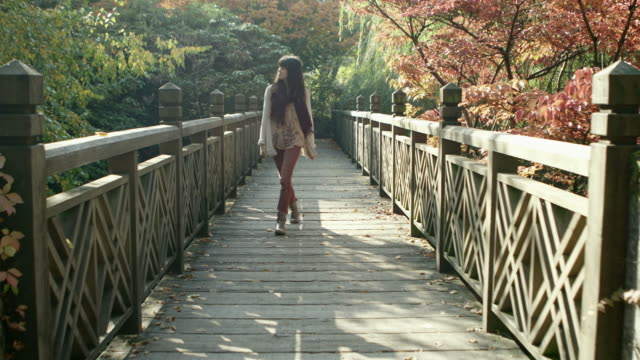A young woman walking in the park crosses a bridge and comes towards the camera video