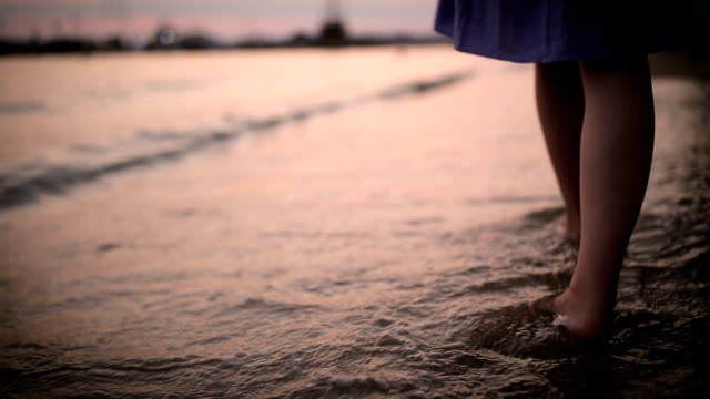 Young woman walking in the surf on the beach at sunset