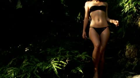vídeos y material grabado en eventos de stock de joven mujer caminando en una piscina tropical - parte del cuerpo humano
