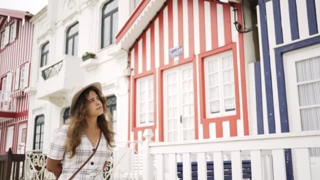 vídeos de stock e filmes b-roll de young woman walking near colorful buildings - aveiro