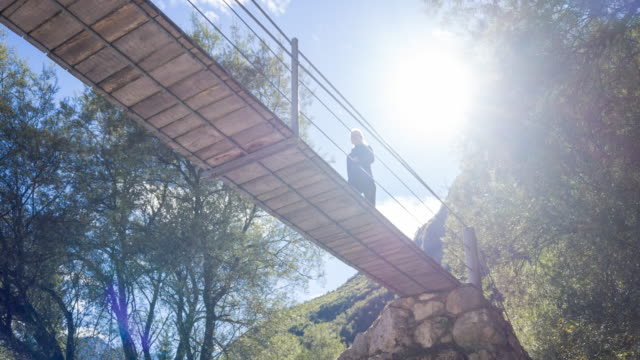 Young woman walking on a wooden suspension bridge Young woman walking on a wooden suspension bridge. suspension bridge stock videos & royalty-free footage
