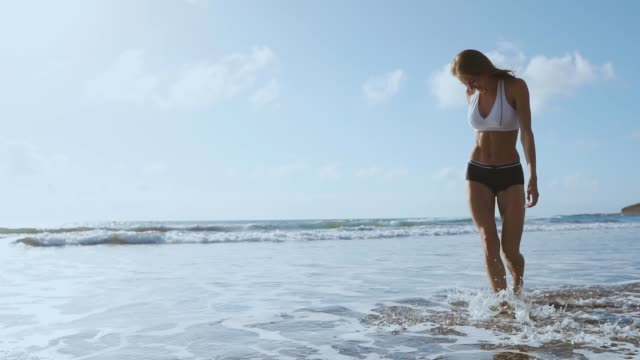 Young woman walking on beach.
