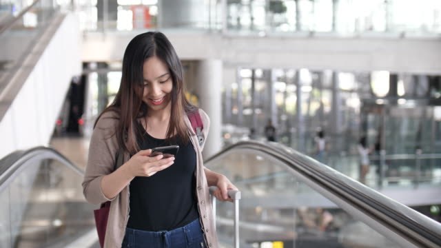 young woman walking on escalator and using phone, business travel - escalator video stock e b–roll