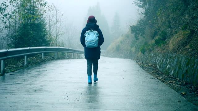vídeos de stock e filmes b-roll de young woman walking on foggy road lonely - mochila saco