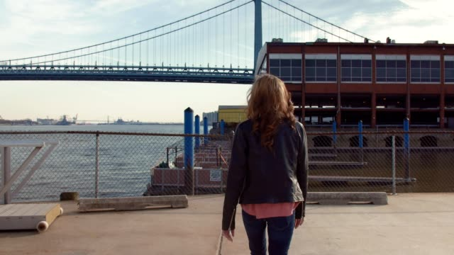 Young woman walking on pier by large suspension bridge video