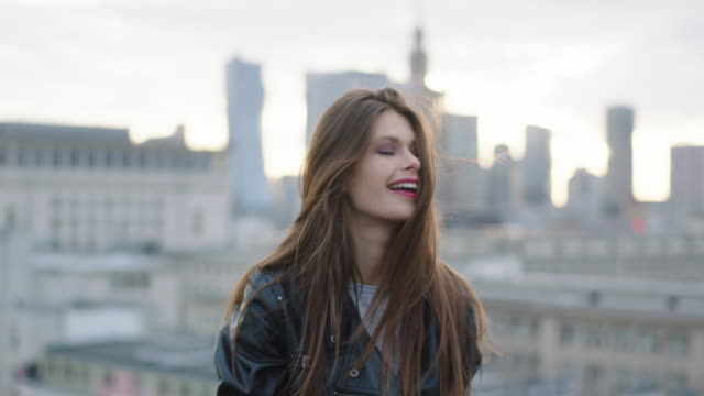 Young woman walking on roof and smilling Pretty woman with long straight brown hair looking at camera. Big city in background. red lipstick stock videos & royalty-free footage