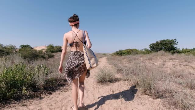 junge frau zu fuß auf sandstrand, tragetasche. rückansicht - menschlicher rücken stock-videos und b-roll-filmmaterial