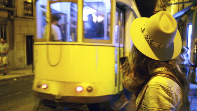 vídeos de stock e filmes b-roll de young woman walking on street at night - people lisbon