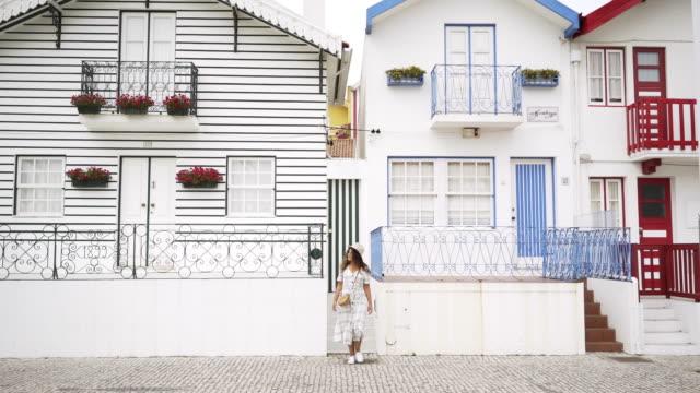 vídeos de stock e filmes b-roll de young woman walking on street of costa nova - aveiro