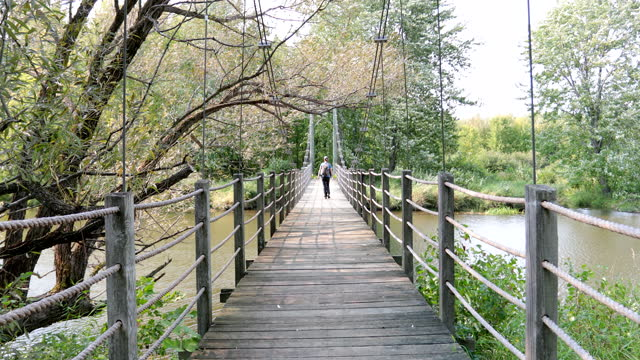 Young Woman Walking on Suspension Bridge in Summer