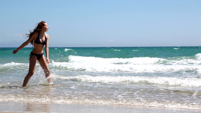 Young woman walking on the beach Young woman walking on the beach and play with water aegean sea stock videos & royalty-free footage