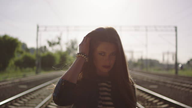 Young woman walking on the railway. Rock and roll style. video