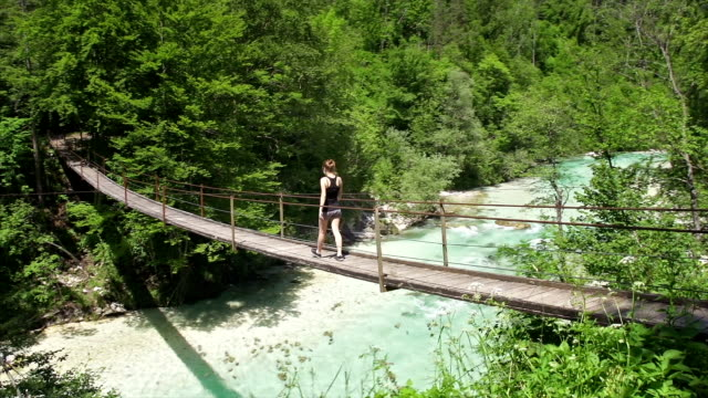 Young woman walking over a hanging bridge video