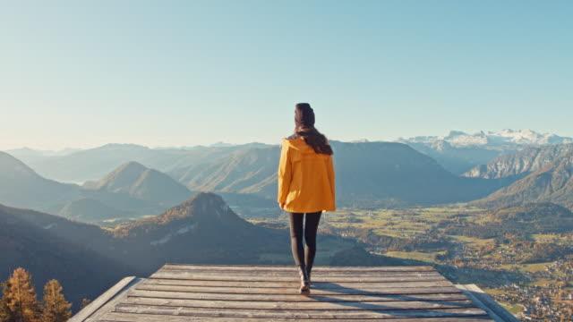 vídeos de stock, filmes e b-roll de senhora mulher nova que anda à borda da plataforma que negligencia a vista ensolarada, cénico da paisagem da montanha, montanha do vencido, áustria - áustria