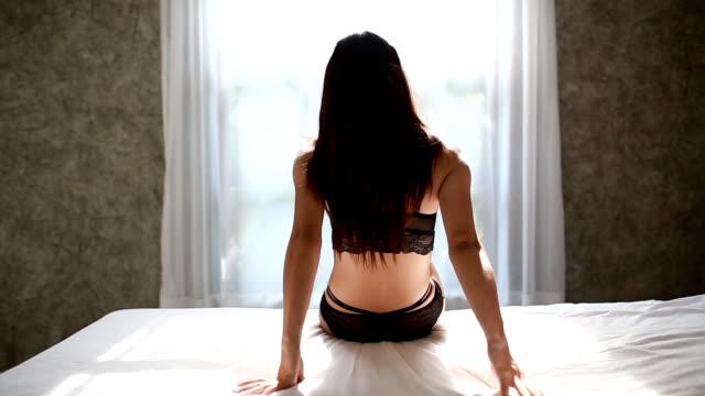 Mujer joven caminando a la ventana - vídeo